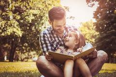 唯一父亲坐与小女儿的草 免版税库存图片