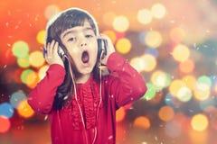 唱歌一个小圣诞老人的女孩的画象,当听到音乐时 免版税库存图片
