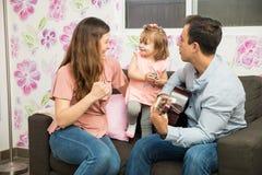 唱歌与一把声学吉他一起的家庭 库存图片