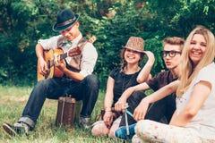 唱歌与吉他一起的愉快的少年 图库摄影