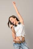 唱歌与话筒的十几岁的女孩跳舞 免版税库存照片