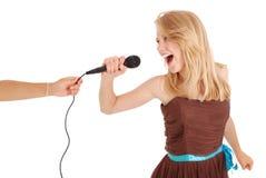 唱歌与话筒的愉快的年轻美丽的女孩 免版税库存照片