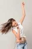 唱歌与话筒的跳舞的十几岁的女孩 免版税库存照片
