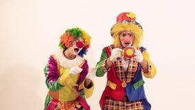 唱歌两三个高兴的滑稽的小丑使用和,当玩具吓唬他们 股票视频