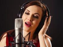唱歌入一个专业话筒 免版税库存照片