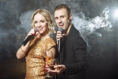 唱歌入在俱乐部的一个话筒的一对年轻愉快的夫妇的画象 库存图片