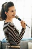 唱歌入在顶楼公寓的一个话筒的愉快的少妇 免版税库存图片
