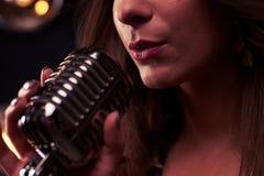唱歌入话筒的妇女极端特写镜头 免版税库存照片