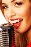 唱歌入话筒的美丽的妇女 图库摄影