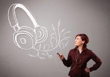 唱歌和听到与抽象headpho的音乐的少妇 免版税库存图片