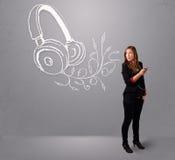 唱歌和听到与抽象headpho的音乐的少妇 库存图片