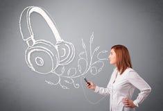 唱歌和听到与抽象headpho的音乐的少妇 库存照片