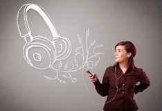 唱歌和听到与抽象headpho的音乐的少妇 免版税图库摄影