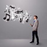 唱歌和听到与音乐会的音乐的可爱的年轻人 库存照片