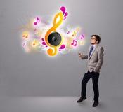 唱歌和听到与音符的音乐的年轻人 免版税图库摄影