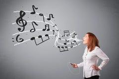 唱歌和听到与musica的音乐的可爱的小姐 免版税库存照片