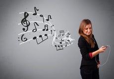 唱歌和听到与musica的音乐的可爱的小姐 免版税图库摄影