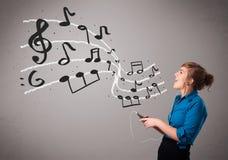 唱歌和听到与musica的音乐的可爱的小姐 库存照片