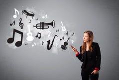 唱歌和听到与musica的音乐的美丽的少妇 免版税库存照片