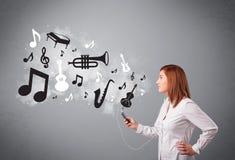 唱歌和听到与musica的音乐的美丽的少妇 免版税库存图片