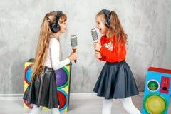 唱歌和听到在耳机的音乐的滑稽的孩子 骗局 免版税库存照片
