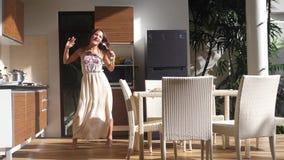 唱歌和跳舞在厨房里的愉快的年轻女人,当做早餐在晴朗的早晨时 60fps 慢的行动 股票录像