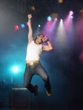 唱歌和跳跃在阶段的年轻人 免版税库存照片