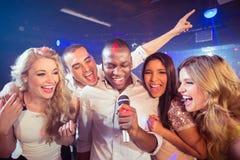 唱歌在卡拉OK演唱的愉快的朋友 免版税图库摄影
