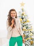 唱歌在圣诞树前面的愉快的少妇 免版税库存照片
