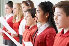 唱歌在学校合唱团的小组孩子 免版税图库摄影