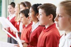唱歌在学校合唱团的小组孩子 库存图片