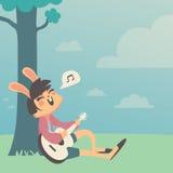 唱歌在树下的兔宝宝女孩 免版税库存照片
