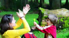 唱歌在森林里的母亲和儿子 免版税图库摄影