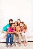 唱歌在沙发的小组孩子 免版税库存照片
