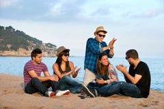 唱歌在海滩的组朋友。 免版税库存照片
