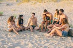 唱歌在海滩的小组朋友在日落 免版税库存照片