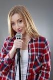 唱歌在话筒的一名美丽的白肤金发的妇女 库存图片