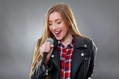 唱歌在话筒的一名美丽的白肤金发的妇女 图库摄影