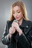 唱歌在话筒的一名美丽的白肤金发的妇女 免版税库存照片
