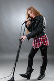 唱歌在话筒的一名美丽的白肤金发的妇女 免版税库存图片