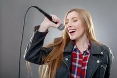 唱歌在话筒的一名美丽的白肤金发的妇女 免版税图库摄影