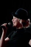 唱歌在话筒的妇女 图库摄影