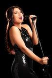 唱歌在话筒的美丽的女歌手 免版税图库摄影