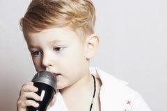 唱歌在karaoke.music的microphone.child的小男孩 免版税库存照片