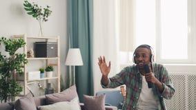 唱歌嬉戏的非裔美国人的人获得乐趣在家在遥控和跳舞的平展放松在好的光 股票视频