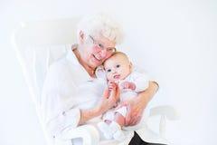唱歌对新出生的孙子的美丽的祖母 免版税图库摄影