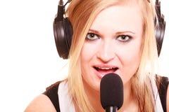唱歌对话筒佩带的耳机的妇女 库存照片