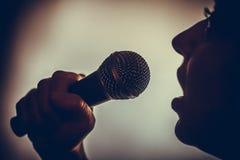 唱歌对话筒的妇女 免版税图库摄影