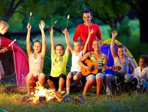 唱歌曲的愉快的孩子在阵营火附近 图库摄影