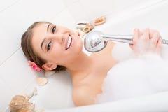 唱歌温泉:美好愉快微笑的女孩性感的妇女说谎的放松在与泡沫藏品阵雨的浴在获得的手上乐趣 免版税库存照片